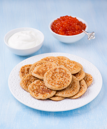 Buckwheat blini with red caviar and sour cream on white plate, selective focus Stock Photo