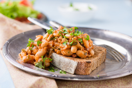 beans on toast: Stewed white beans in tomato sauce on toasted bread, selective focus, closeup