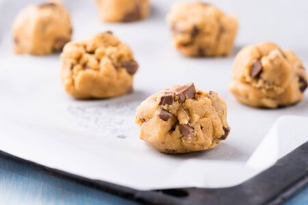 Raw cookie dough on a baking tray with parchment paper, selective focus Stock Photo