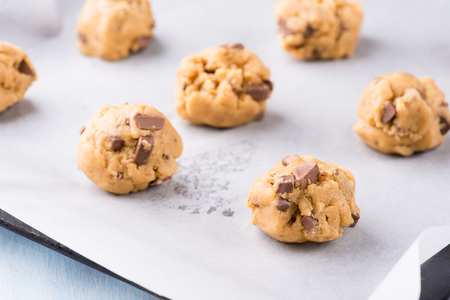 homemade cookies: Raw cookie dough on a baking tray with parchment paper, selective focus Stock Photo