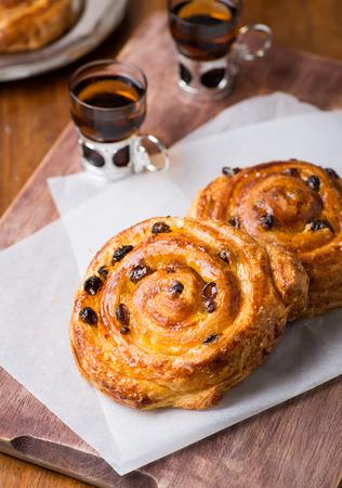 pasteleria francesa: Pasas pain au caseras frescas sobre fondo de madera, enfoque selectivo