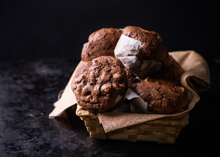 muffin: Chocolate muffins with nuts in basket, on dark background, selective focus Stock Photo