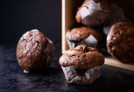 dark chocolate: Chocolate muffins with nuts on dark background, selective focus
