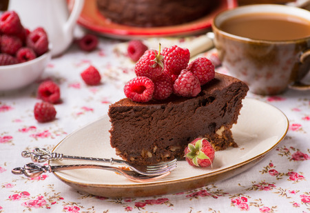 Homemade chocolate cake with raspberry on plate, cup of coffee and barries on side, selective focus