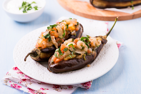imam: Imam Bayildi. Eggplants stuffed with vegetables on white plate. Turkish food. Slective focus. Stock Photo