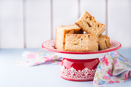 cakestand: Homemade apple cake, slices on red cakestand, copy space, selective focus