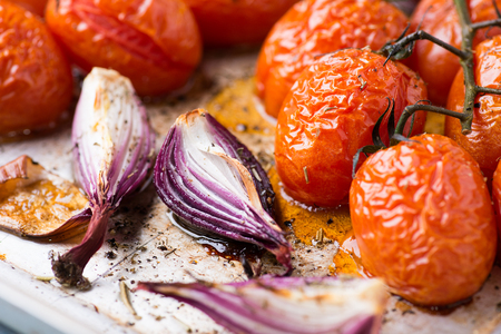 baking tray: Oven roasted onions and tomatoes on metal baking tray, top view, selective focus Stock Photo