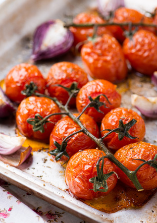 lunch tray: Oven roasted tomatoes and onions on metal baking tray, top view, selective focus