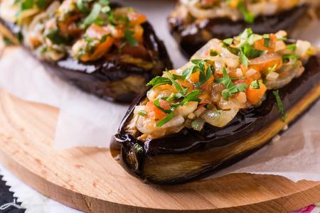 imam: Imam Bayildi. Eggplants stuffed with vegetables on wooden board. Turkish food, closeup, selective focus