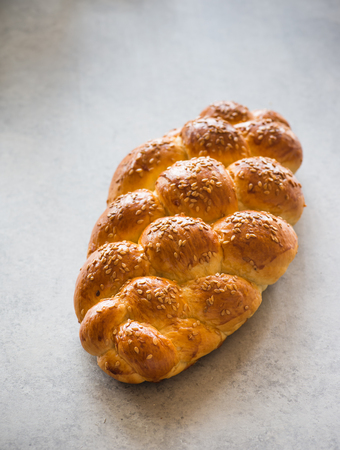 challah: Homemade challah bread with sesame seeds over grey background, selective focus