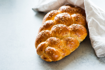 Homemade challah bread with sesame seeds over grey background, selective focus