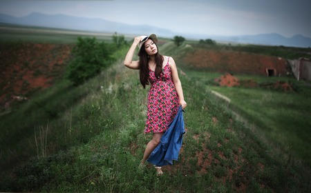 across: Beautiful girl in a hat walks across the field on a cloudy day
