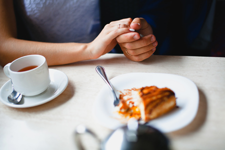 held: Couple in a cafe held by the hand, a piece of cake  at foreground Stock Photo