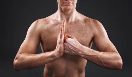 master: muscular hands clasped yoga master in the studio