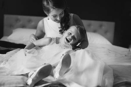 same: Mother and daughter in the same wedding dresses having fun on the bed Stock Photo