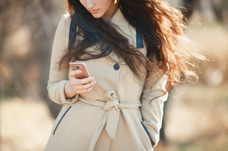 flying hair: Girl with flying hair in the coat looks in the smartphone