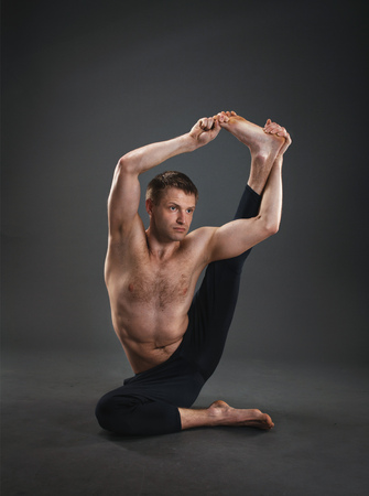 man power: yoga master in the studio shows yoga postures