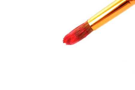 Brush in red paint closeup photo