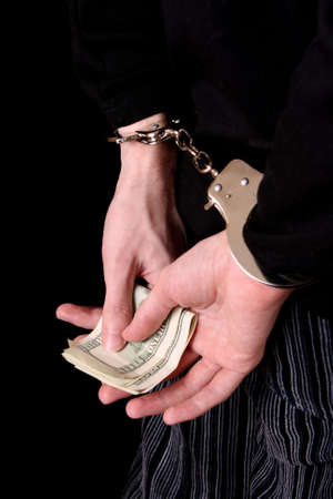 Man with handcuffs and dollars on black Stock Photo - 6197214