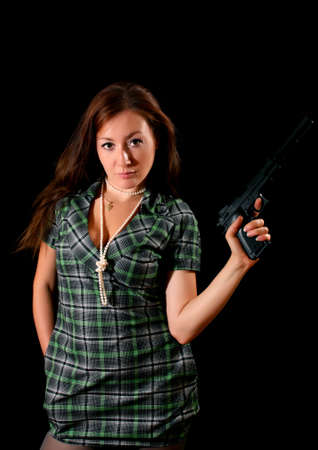 Young woman with pistol on black background Stock Photo - 6255395