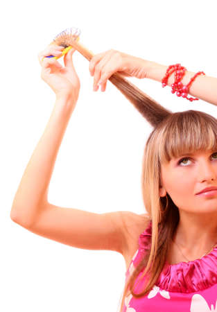 Beautiful young woman combing her hair photo