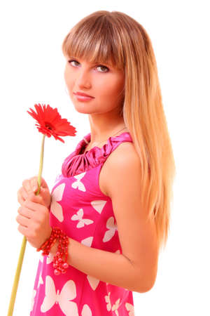 Beautiful young girl in pink dress with red flower photo