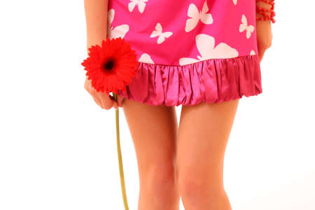 Beautiful legs with a Red Gerber Daisy flower isolated on white background photo