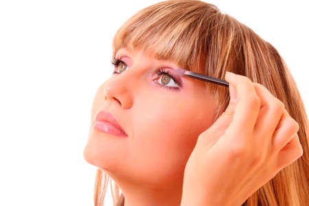 beautiful young woman applying makeup with brush photo