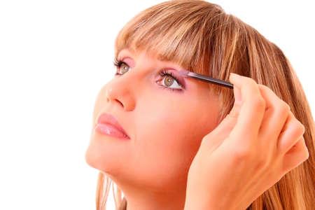 beautiful young woman applying makeup with brush photo