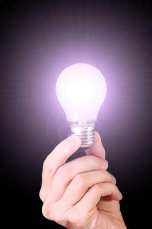 hand with lightbulb on black background photo