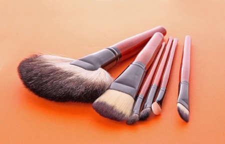 cosmetic brushes on the orange background photo