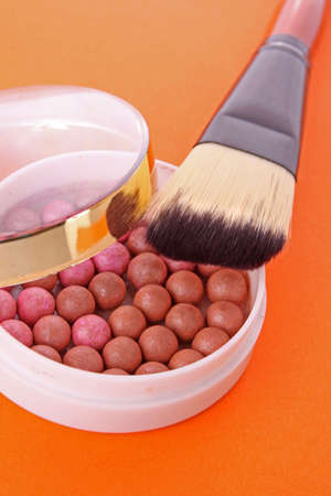 corpuscle: cosmetic brush and rouge  on the orange background