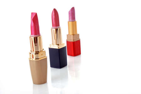three colored lipsticks on white background photo