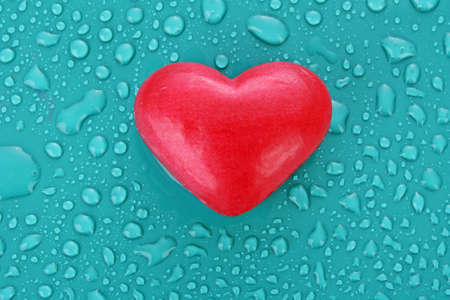 Soap in heart shape on blue water drops background photo