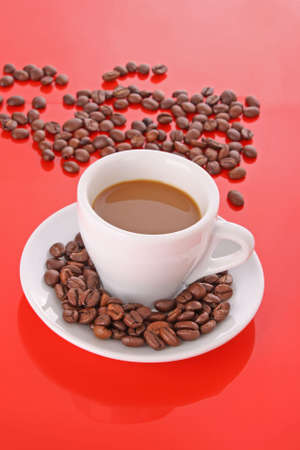 Small white  cup of coffee with coffee grain   on red background photo