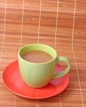 Coffee with milk color cup  on bamboo straws background photo