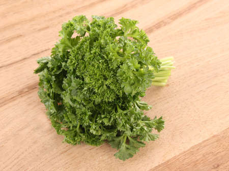 Bouquet of parsley on wooden background photo