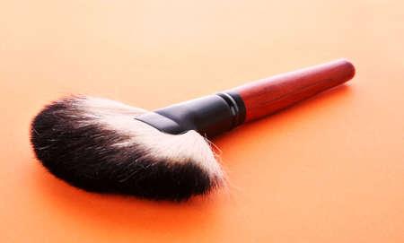 cosmetic brush on the orange background photo
