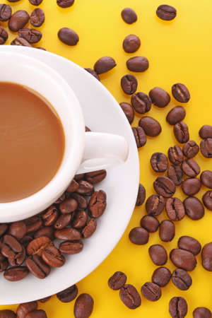 Small white cup of coffee with coffee grain on yellow background photo