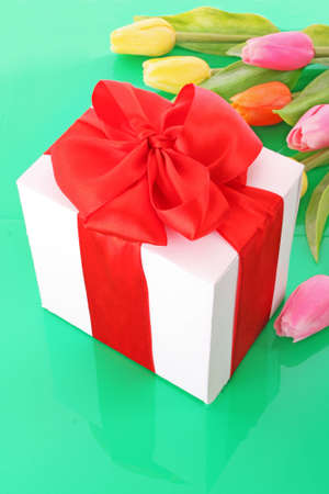 Yellow and pink tulips and gift box on green background Stock Photo - 6801597