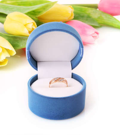 metal spring: Gold  engagement ring in box on the flowers background Stock Photo