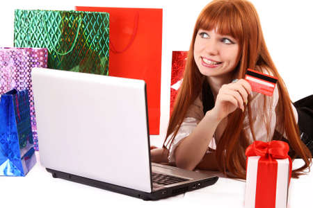 Beautiful, young, redhair woman with color shopping bags shopping over internet. On white background.