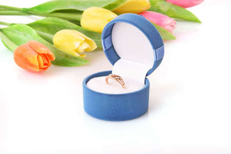 Gold  engagement ring in box on the flowers background photo