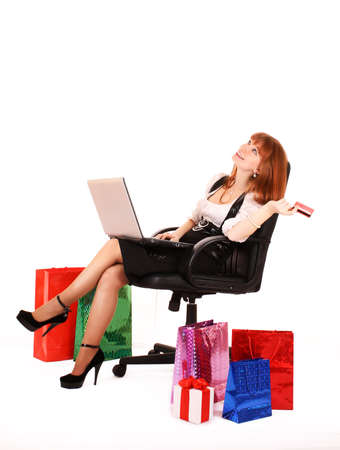 Beautiful, young, redhair woman with color  shopping bags shopping over internet.  On white background. Stock Photo - 6880296