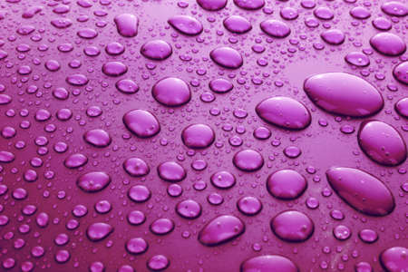 Violet water drops background with big and small drops photo