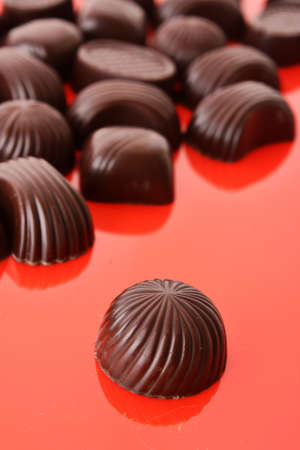 Assorted chocolate candies on red background photo