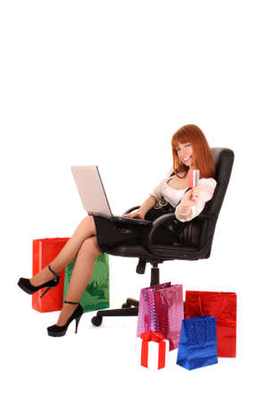 boxing day sale: Beautiful, young, redhead woman with color shopping bags shopping over internet. On white background.