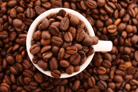 Small white cup of coffee with coffee grain on grain background photo