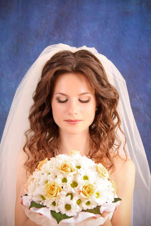 Beautiful woman with in  wedding dress over blue studio background photo