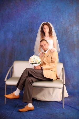 Bride and groom over blue studio background photo